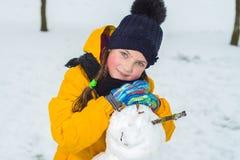 Portret van een mooi meisje in de winter het gelukkige kind maakt een sneeuwman royalty-vrije stock fotografie