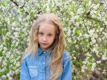 Portret van een mooi meisje in een denimoverhemd met een ernstige gelaatsuitdrukking in een kersenboomgaard Stock Fotografie