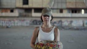 Portret van een mooi meisje die in een camouflage GLB en witte t-shirt een kroon houden bekijkend de camera De vrouw van de strij stock video