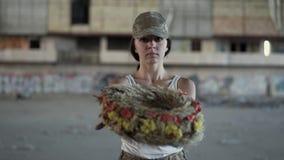 Portret van een mooi meisje die in een camouflage GLB en witte t-shirt een kroon houden bekijkend de camera De vrouw van de strij stock footage