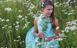 Portret van een mooi meisje in een blauwe kleding en ornamenten die in openlucht stellen Stock Afbeelding