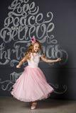 Portret van een mooi meisje in een roze prinseskroon op donkere bedelaars Royalty-vrije Stock Afbeelding