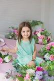Portret van een mooi meisje in een turkooise kleding dichtbij bloemen in een studio stock fotografie