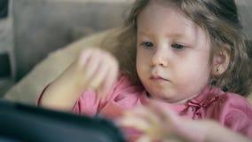 Portret van een mooi meisje, een kind dat op de bank onder de deken ligt stock videobeelden