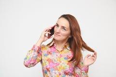 Portret van een mooi meisje in een kleurrijk overhemd die op telefoon het spelen met haar spreken Op een witte achtergrond Bruine royalty-vrije stock foto's