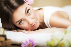 Portret van een mooi meisje in een kuuroord Verzacht blik Bloemen in haar Aromaolie Massagekabinet Het concept gezondheid en scho royalty-vrije stock foto