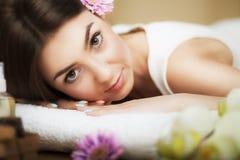 Portret van een mooi meisje in een kuuroord Verzacht blik Bloemen in haar Aromaolie Massagekabinet Het concept gezondheid en scho stock afbeeldingen