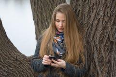 Portret van een mooi meisje met een telefoon in de vroege lente in openlucht Stock Foto's