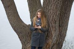 Portret van een mooi meisje met een telefoon in de vroege lente in openlucht Royalty-vrije Stock Afbeeldingen