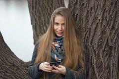 Portret van een mooi meisje met een telefoon in de vroege lente in openlucht Royalty-vrije Stock Fotografie