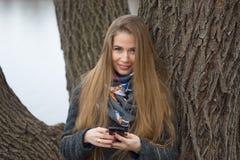 Portret van een mooi meisje met een telefoon in de vroege lente in openlucht Stock Afbeeldingen