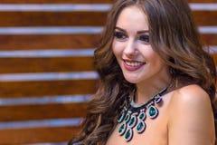 Portret van een mooi meisje met een feestelijke samenstelling en met een smaragdgroene halsband op haar hals met het doordringen  stock afbeelding