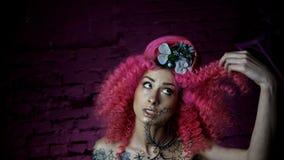 Portret van een mooi meisje met krullend roze haar modieus kapsel L stock videobeelden