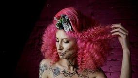 Portret van een mooi meisje met krullend roze haar modieus kapsel L stock video