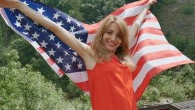 Portret van een mooi meisje in een rode kleding tegen de achtergrond van bosbergen en de hemel De Onafhankelijkheidsdag van de V. stock videobeelden