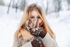 Portret van een mooi meisje in een sjaal en handschoenen in de winterpari Royalty-vrije Stock Afbeeldingen
