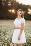 Portret van een mooi meisje in een witte kleding op een bloeiend gebied Gebied van bloemen De zomer Eenheid met aard stock afbeeldingen