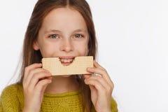 Portret van een mooi 8 ??njarigenmeisje in een sweater en met een wafeltje in haar handen Witte achtergrond royalty-vrije stock afbeeldingen