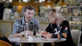 Portret van een mooi paar in koffie, vriend en meisje op een datum in comfortabele koffie die desserts eten en koffie drinken stock video