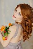 Portret van een mooi roodharig meisje die met blauwe ogen a houden stock afbeelding