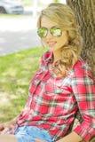 Portret van een mooi sexy meisje met grote mollige lippenkrullen in denimborrels en een overhemd in zonnebril die dichtbij een bo Royalty-vrije Stock Foto