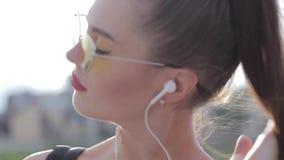 Portret van een mooi sportenmeisje in hoofdtelefoons en met een telefoon stock video