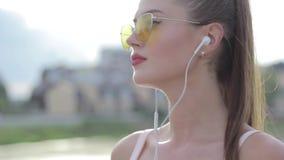 Portret van een mooi sportenmeisje in hoofdtelefoons en met een telefoon stock videobeelden