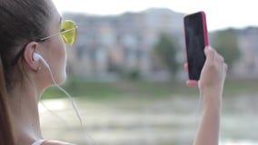 Portret van een mooi sportenmeisje in hoofdtelefoons en met een telefoon stock footage
