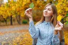Portret van een mooi, zoet, vrolijk meisje dat in het Park in de herfstseizoen loopt royalty-vrije stock afbeelding