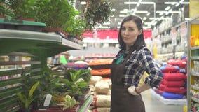 Portret van een mooie arbeider die van de vrouwenopslag de camera onderzoeken stock video