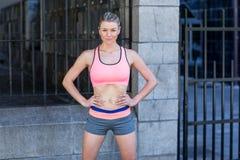 Portret van een mooie atleet met haar handen op haar heupen stock foto