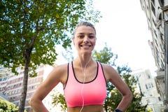 Portret van een mooie atleet met haar handen op haar heupen stock afbeeldingen