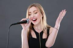 Portret van een mooie blonde jonge vrouw die in micropho zingen Stock Foto's
