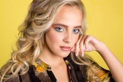 Portret van een mooie blonde vrouw met een mooie kapsel en een make-up Studiofoto op een gele achtergrond Stock Foto