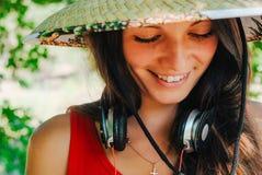Portret van een mooie donkerbruine vrouw in een strohoed met hoofdtelefoons Close-up Stock Fotografie