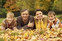 Gelukkige familie die in de herfstpark liggen Stock Afbeeldingen