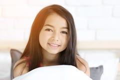 Portret van een mooie gelukkige het glimlachen meisjesrust op het bed Stock Afbeeldingen