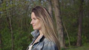 Portret van een mooie glimlachende jonge vrouw die een denimjasje dragen die op een mooie zonnige dag in openlucht lopen charming stock videobeelden