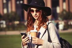 Portret van een mooie glimlachende vrouw die mobiele telefoon met behulp van terwijl het houden van koffiekop op een stadsstraat royalty-vrije stock foto