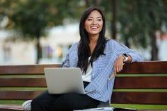 Portret van een mooie het lachen Aziatische vrouwelijke studentenzitting Royalty-vrije Stock Afbeeldingen