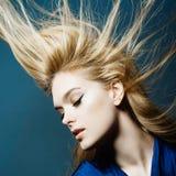 Portret van een mooie jonge blondevrouw in studio op een blauwe achtergrond met het ontwikkelen van haar Stock Foto's