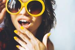 Portret van een mooie jonge donkerbruine vrouw met volledige lippen in gele retro zonnebril en gele vernis op de spijkers Stock Afbeeldingen