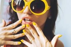 Portret van een mooie jonge donkerbruine vrouw met volledige lippen in gele retro zonnebril en gele vernis op de spijkers Stock Fotografie