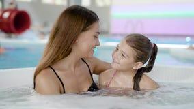 Portret van een mooie jonge moeder met aanbiddelijke dochter in hete ton stock footage