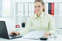 Portret van een mooie jonge secretaresse die bij het laptopsitting op kantoor werken Stock Fotografie