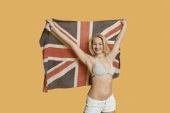 Portret van een mooie jonge vrouw die Britse die vlag met wapens houden over gekleurde achtergrond worden opgeheven Stock Afbeelding