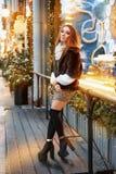 Portret van een mooie jonge vrouw die op de straat dichtbij het elegant verfraaide Kerstmisvenster, feestelijke stemming stelt royalty-vrije stock fotografie