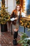 Portret van een mooie jonge vrouw die op de straat dichtbij het elegant verfraaide Kerstmisvenster, feestelijke stemming stelt stock foto's