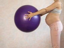 Portret van een mooie jonge zwangere vrouwenoefeningen met rode fitball in de gymnastiek Het uitwerken en geschiktheid, stock foto's
