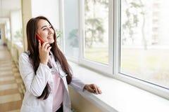 Portret van een mooie medische arts die op de telefoon spreken MEDISCH concept stock fotografie